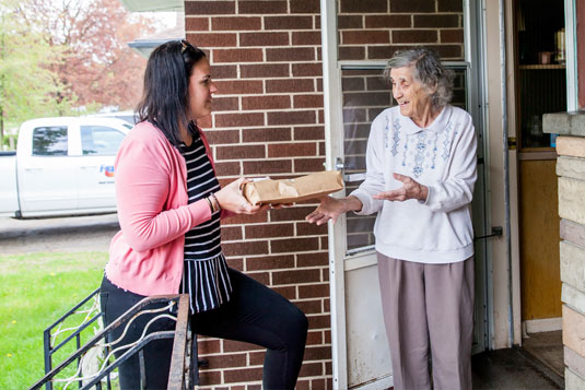 A woman delivering a meal to an older woman at her front door