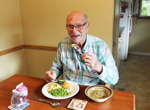 A seated older man enjoying a meal at his home