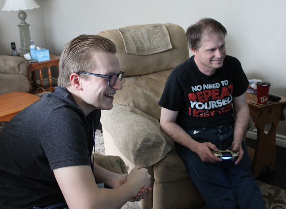 Two smiling young men playing video games in a living room