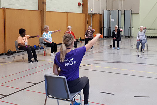 A seated female exercise instructor leading a class of seated adults in a gym