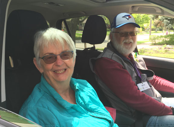 An smiling older couple in the front seats of a car