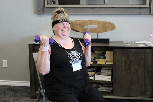 A smiling seated woman lifting hand weights