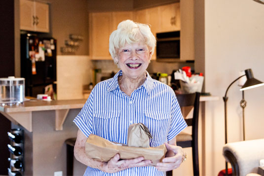 A smiling woman standing with a meal in her home