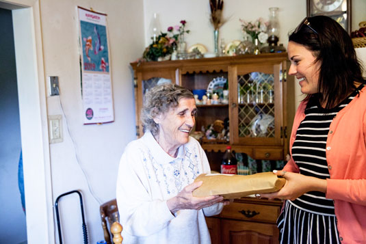 A smiling woman delivering a meal to an older smiling woman in her home