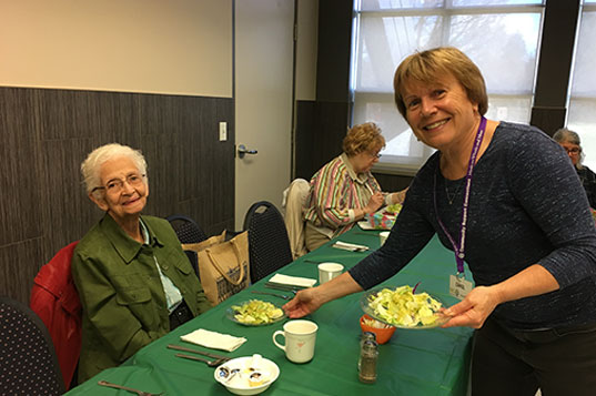 A smiling woman serves salad to a seated older woman