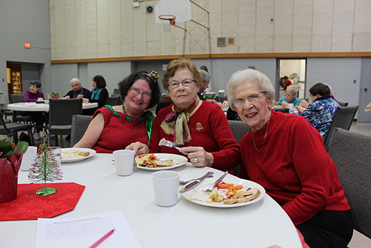 Three older women enjoying a meal in a gym together