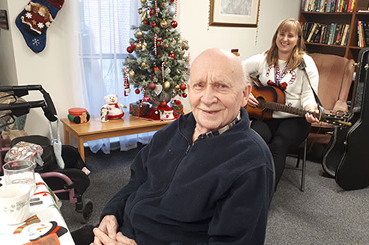 A happy older man listening to a young woman playing the guitar
