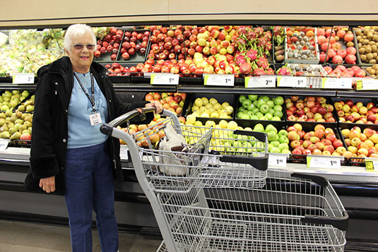 An older woman with a shopping cart in front of a fruit aisle