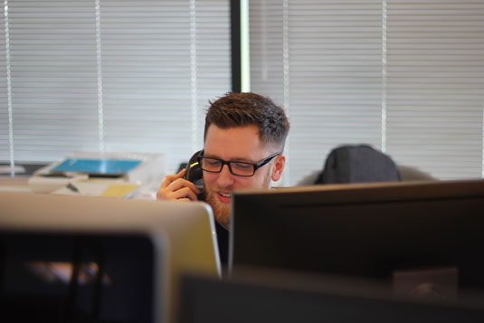 A smiling bearded man on a telephone while at a computer