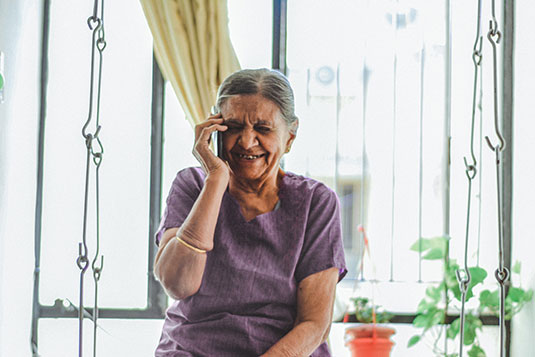 A laughing older woman on her mobile phone