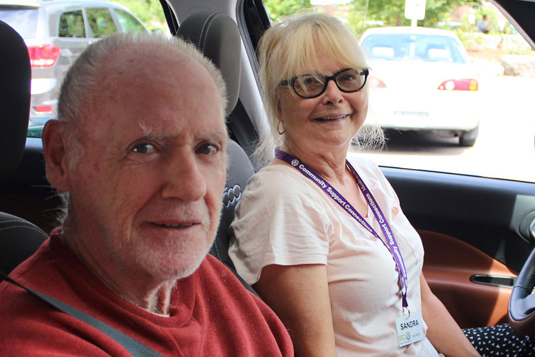 A female volunteer and an older male client in the front seats of a car