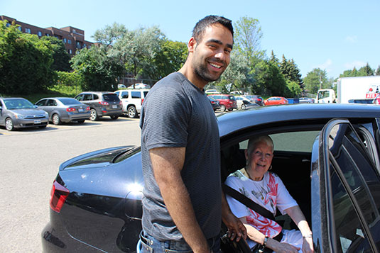 A smiling young male volunteer a opening a car door for a happy older woman
