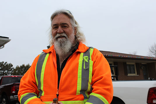 A smiling, bearded man in a work safety jacket
