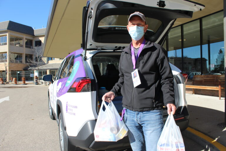 A volunteer delivering groceries from their car's trunk